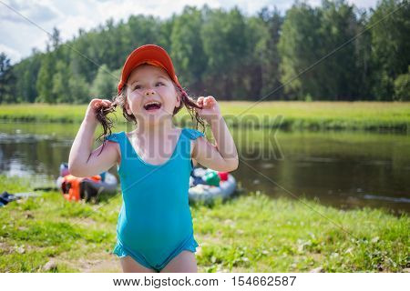 Little girl in swimsuit laughs near river with inflatable boats out of focus during camping trip at summer