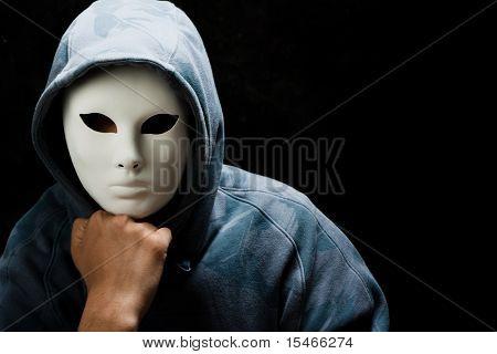 young man wearing mask and hood, studio shot