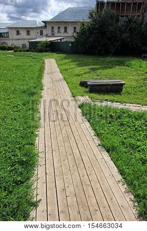 beautiful wooden walking path paved with wooden board with green grass