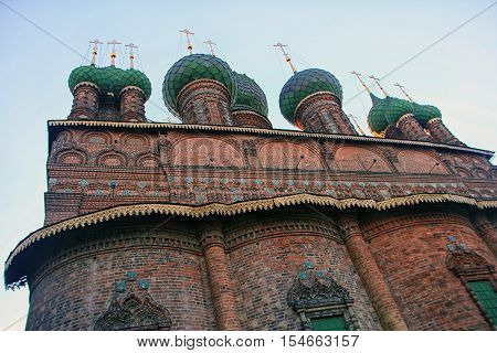 old beautiful red-brick Russian Orthodox Church with its green domes of the 16th century in Yaroslavl