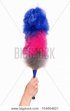 Hand holding broom for cleaning or soft colorful duster with plastic handle, isolated on white background. Cleaning woman holding colorful synthetic duster.