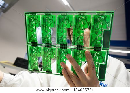 Saint-Petersburg Russia - November 2 2016: Manufacturer of automotive security systems Starline. Integrated circuit board close-up in the hands of a woman engineer.