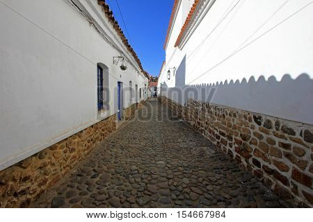 Cobblestone street and white colonial houses in Sucre, capital of Bolivia.