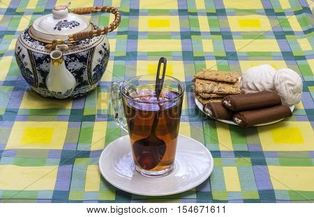 On the table mishandled colored tablecloth. On the tablecloth is a glass cup with tea tea and sweets in the basket are