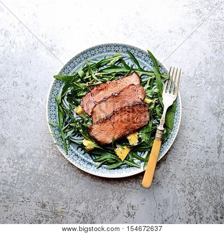 salad of arugula and roast beef on a gray background