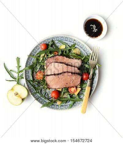 chopped beef steak medium, Ruccola Arugula salad with tomatoes and walnuts, on gray plate, isolated