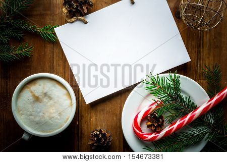 Christmas coffee latte or cappuccino with a notebook for list of gifts or a wishlist, Christmas tree branch, pine cones and Christmas balls, vertical, copy space