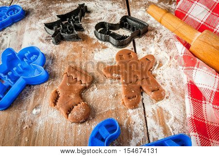 Making cookies for Christmas and New Year. Fun food for kids, a snack for a party. Unbaked cookies, cookie cutters, rolling pin, flour, towel