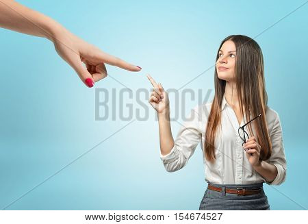 A confident businesswoman pointing with her index finger at the giant hand, pointing at her, all isolated on the light-blue background. Business and management. Success and promotion. Corporate culture.