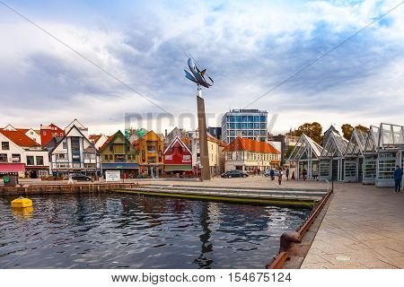 STAVANGER, NORWAY - OCTOBER 10, 2016: People at the quay port with many restaurants and pubs in the city centre of Stavanger. Stavanger is one of most famous cruise travel destinations in Europe.
