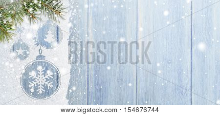 christmas card or new year background made of xmas symbols handwritten on snow with fir-tree branches and blue wooden table