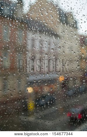 Rain drops on the window. Street view through the window at a rainy day.