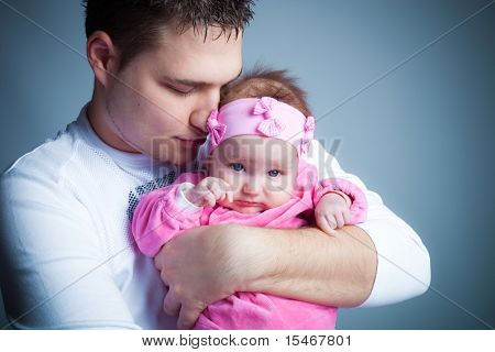 young father hold his baby girl in arms, studio shot
