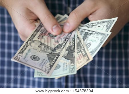 Hands holding US dollar bank notes a blue shirt in the background. Short depth of focus