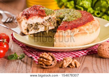 Calzone with walnuts and endive on wooden table.