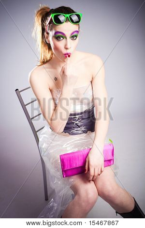 young woman in plastic dress and heavy make up sending kiss with one finger studio shot