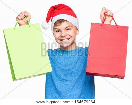 Half-length portrait of smiling teen boy wearing Santa Claus hat, surprised. Caucasian tenager in blue t-shirt, holding shopping bags. Holiday Christmas concept - happy cute child isolated on white background.