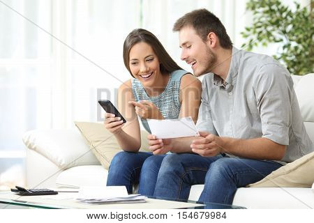 Couple doing accounting on line with a phone bank app sitting on a couch in the living room at home