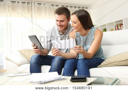 Happy couple checking bank account on line in a tablet sitting on a couch in the living room at home