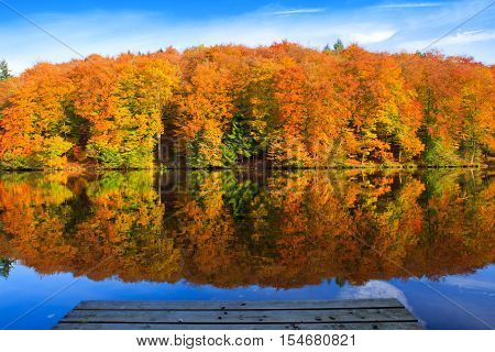 Lake with a jetty by the beach and reflections of autumn colors in the water. Jetty on a German lake.