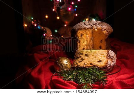 Cut to pieces homemade panettone - traditional sweet bread for Christmas and New Year with fruit and spices drizzled with icing sugar on dark holiday background with pine branch golden ball and blurred colorful lights. Selective focus. Horizontal.