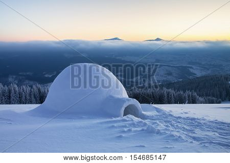 Marvelous huge white snowy hut igloo the house of isolated tourist is standing on high mountain far away from the human eye.