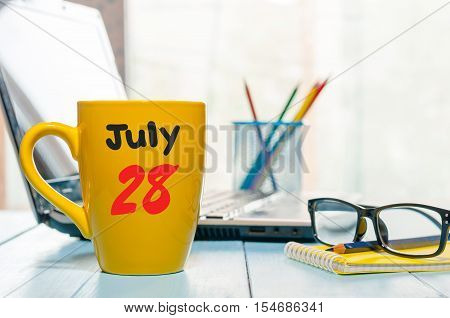 July 28th. Day 28 of month, color calendar on morning coffee cup at hard worker workbench background. Summer time. Empty space for text.