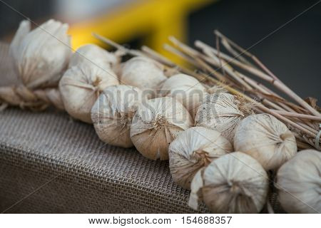 Plait Of Fake Decorative Garlic Laying On Piece Of Cloth. Bunch Of Garlic Made Of Paper Craft Kitchen Design Element