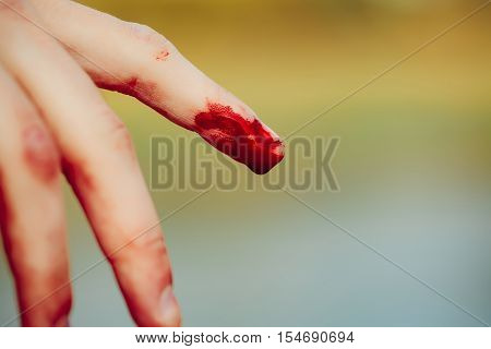 index finger on human hand or palm is cut hurt and bleeding with bright red blood outdoor on blurred or defocused green background