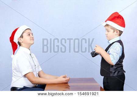 The younger brother in a cap of Santa Claus is photographing of brother