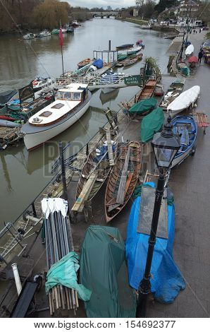 London, England - February 04, 2016: Rowing boats hauled up for maintenance during the winter months at a boatyard along the River Thames at Richmond in London on an overcast and rainy day