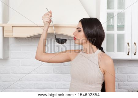 Young beautiful slim girl standing in the kitchen preparing food. A girl  tasting food.