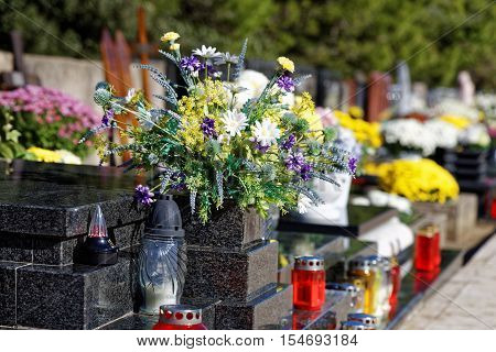 bouquet of flowers and candles on cemetery
