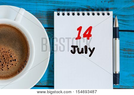 July 14th. Day 14 of month, calendar on business workplace background with morning coffee cup. Summer concept. Empty space for text.