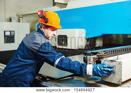 industrial factory worker operates punching machine