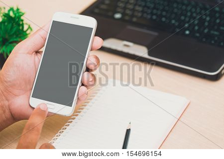 Businessman's hands holding and use mobile phone on on office table