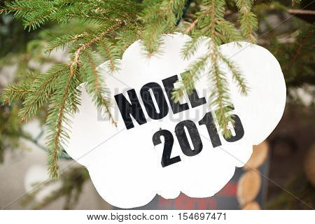 Noel 2015 which translates as Christmas 2015 printed on white board and used as a tree decoration