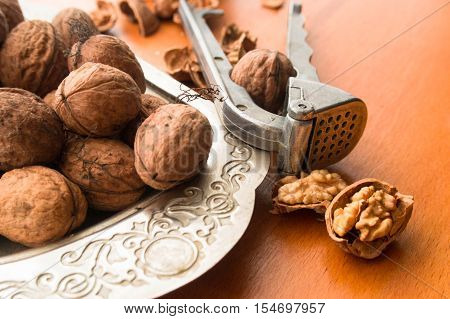 Greek nuts whole and split and the Nutcracker on wood background