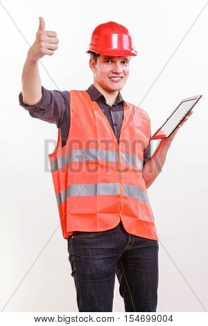 Technological development in company. Young handsome man worker in safety vest and hard hat with tablet. Repairman inspector at work.