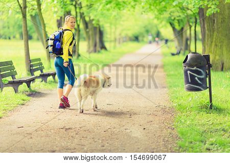 Woman runner running and walking with dog in park summer nature exercising in bright forest outdoors
