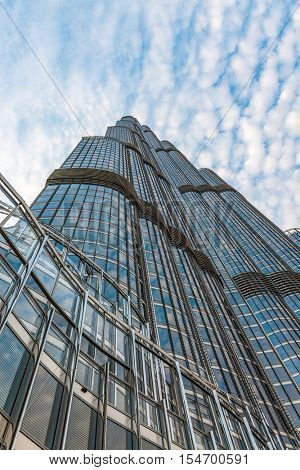 Dubai, U.A.E. - Circa August, 2016: The external facade of the Burj Khalifa, Dubai, the tallest manmade structure in the world viewed looking up from below against a cloudy blue sky