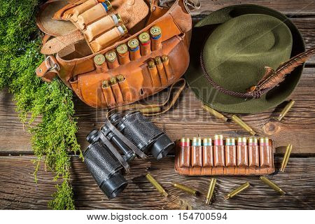 Belt with hunter bullets and binocular on old wooden table