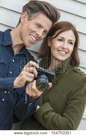 Portrait shot of an attractive, successful and happy middle aged man and woman couple together outside taking photographs with a digital camera