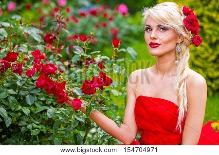 half length portrait of beautiful woman in red dress in park sitting on grass touching flowers and looking at camera