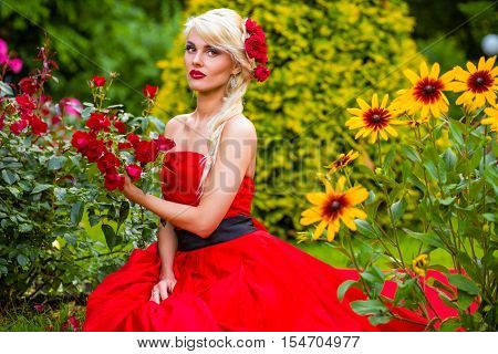 half length portrait of beautiful woman in red dress in park sitting on grass among flower beds, looking at camera