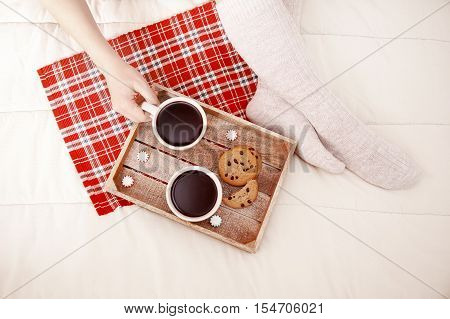 Christmas breakfast in bed. women's feet in warm woolen socks, two cups of coffee and chocolate chip cookies. the concept of cozy Christmas at home. top view