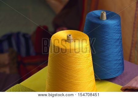Spools of yellow and blue silk thread for woven in silk in Thailand.