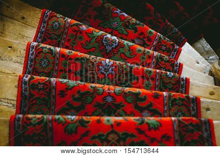 Closeup of ornate French red carpet on stairs.