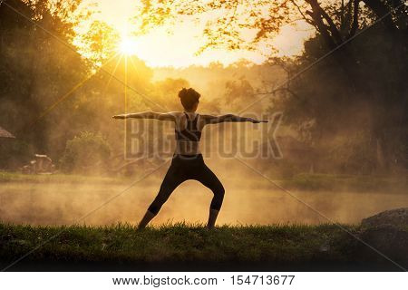Silhouette of a beautiful Yoga woman in the morning at the hot spring park, soft and select focus