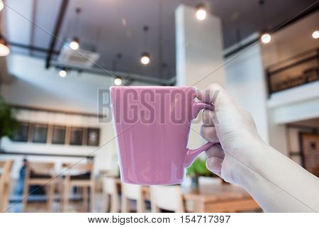 Woman holding coffee cup with abstract blur coffee shop, stock photo